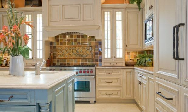 French eclectic kitchen  This French-influenced kitchen is flowing with lots of colors and eclectic items that make cooking any meal fun. The backsplash draws the entire room in with colorful glass tile that is carried through the island and walls. The baby-blue island is offset nicely by the stark white countertop. Care was taken to pick just the right hardware for the kitchen cabinetry