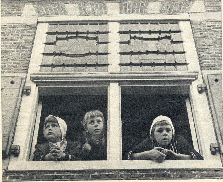 400 jaar Oud-Beijerland - 1959 Ook de jeugd doet enthousiast mee. Vanuit het raam van het oude stadhuis hadden deze 16de-eeuwse meiskes, o.w. het dochtertje van burgemeester Hammer, een prachtig uitzicht op de feestelijkheden. (bron: De Spiegel - 31 oktober 1959)