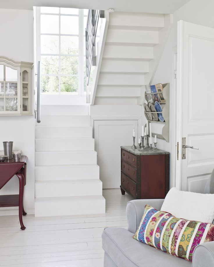 Lovely white stairway with landing that has a large window going clear to the floor.