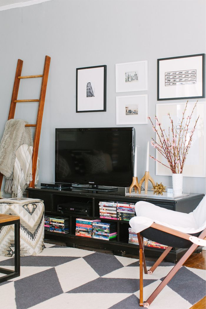 @Alaina Marie Kaczmarski Chicago Apartment Tour // living room // grey // black // white // tv styling // @Lucy Chavez Style Lighting butterfly chair // gallery wall // @Laura Mcfarlane & Georgia ankara pouf // ladder // photography by Stoffer Photography