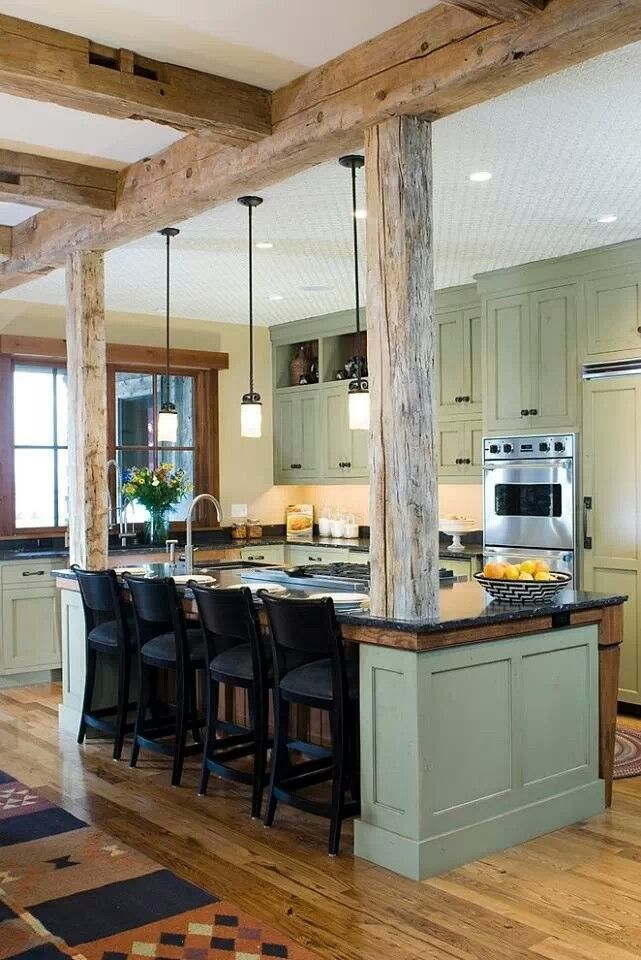 The exposed wood beams of this kitchen are beautifully accented by sage green and hardwood floors.