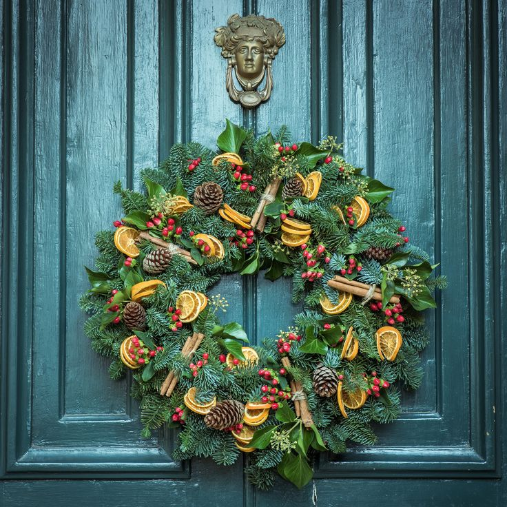 A festive, fall foliage wreath hangs on a dark, green door
