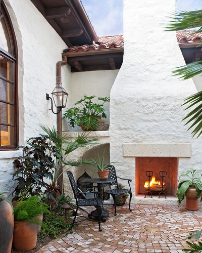 This Spanish-influenced home features a brick patio and a large stucco outdoor
