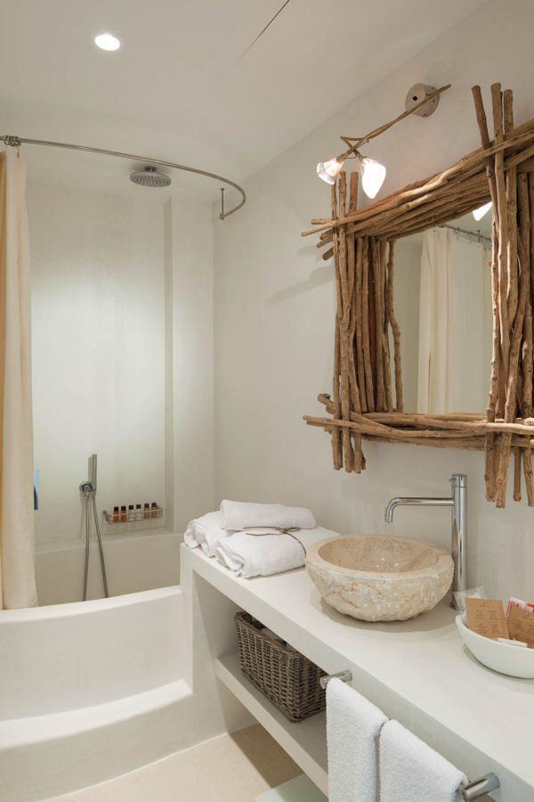 Se mezclan la piedra, la madera y el blanco con detalles como el espejo hecho con ramas. Hotel Es Marès en Formentera