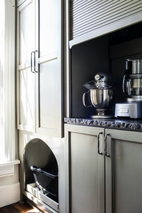 Fabulous kitchen features gray cabinets fitted with a small appliances cabinet finished with a gray garage style door.