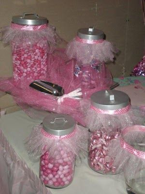 Mason jars filled with candy and decorated with tulle and pink ribbons