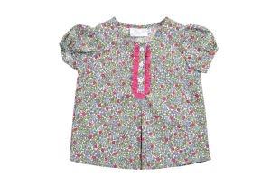 Blusa para bebe niña con estampado de florecitas en fucsia, lilas y verdes. Cuello redondo y mangas cortas.
