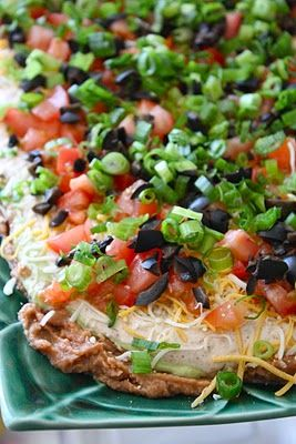 7 Layer Dip Recipe ~ Says: this dip = happy, happy people... you seriously can't go wrong when you bring this crowd pleasing fave to a get together!  You can easily make this a 8, 9 or 10 layer dip as well by adding other goodies like jalapenos, crumbled bacon or cilantro. if you like to add more of one ingredient like more sour cream or olives, then go for it....make it your own.