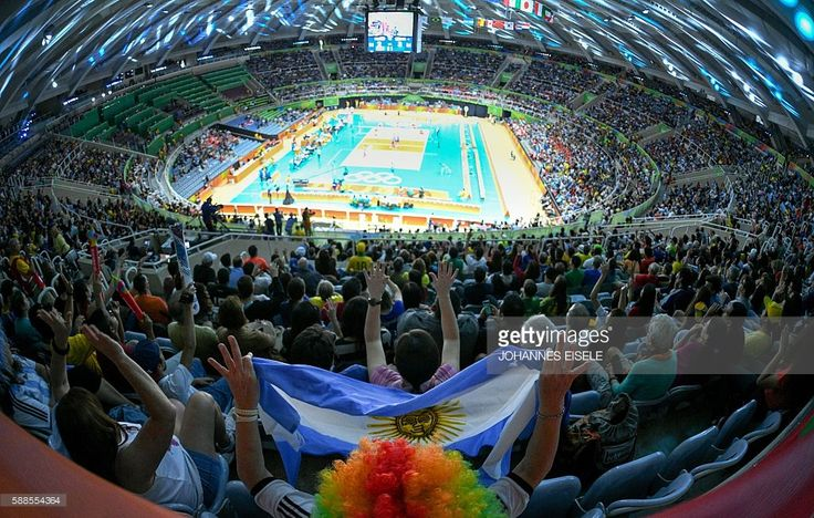 TOPSHOT - Supporters cheer for their teams during the men's qualifying volleyball match between Poland v Argentina at the Maracanazinho stadium in Rio de Janeiro on August 11, 2016, during the Rio 2016 Olympic Games. / AFP / Johannes EISELE