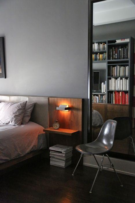 Nella camera padronale il grande letto in legno e pelle disegnato su misura ha lampade e comodini integrati. Sullo specchio è riflessa la grande libreria che ricopre interamente la parete davanti al letto incorniciando la TV a schermo piatto