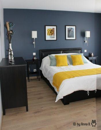 Le jaune des coussins ensoleille le bleu gris foncé de ce mur pour une chambre vitaminée