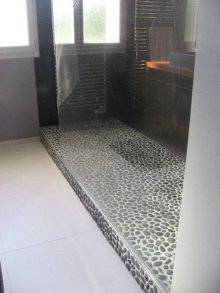 Galets naturels pour le sol de la douche et grandes dalles de carrelage gris foncé pour les cloisons