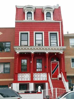 A red house and red stairs and the red and black flag of Trinidad and Tobago, also on Quincy Street, Brooklyn
