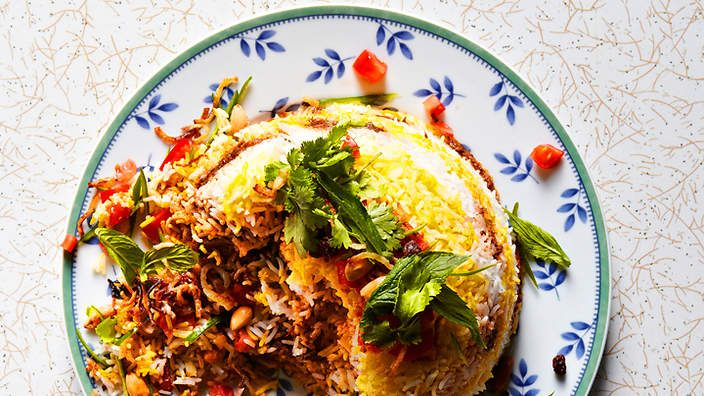 Layered saffron rice and goat curry (bakra biryani)   This recipe for biryani is a marvellous creation of perfectly cooked goat, layered with rice, scattered with tomato, coriander, mint leaves, chilli and almond.