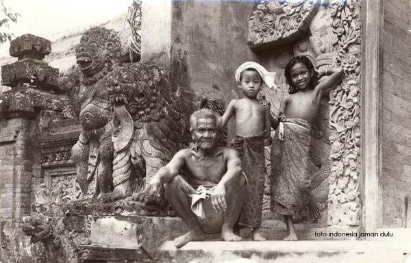 Pria dengan dua anak perempuan di gerbang sebuah pura di Bali ...