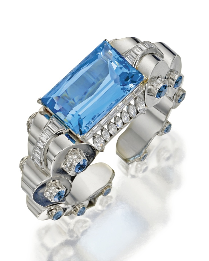Platinum, aquamarine and diamond cuff bracelet, circa 1935. Composed of graduated circular platinum links, set in the center with a French-cut aquamarine weighing approximately 66.25 carats, set at the sides with round aquamarines weighing approximately 8.00 carats, accented by baguette, marquise-shaped and round diamonds weighing approximately 10.00 carats, internal circumference 6 inches