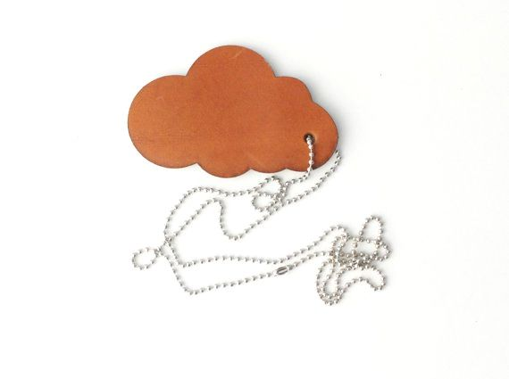 """Leather Necklace Pendant Cloud on silver colored nickelfree surgical steel ballchain. Dream away with these laser cut outs made from thick natural tanned leather. Size:Width 8 cm/3.1"""" Hight 7cm/3.1"""" Thickness 2mm/0.1""""Necklace is a nickel free surgical steel ballchain 90 cm/ 35.4"""" long. Materialnatural tanned leather cognac colored laser cut outNickel free ball chain 35.4""""Logo LABOUR OF ART is marked on the back"""