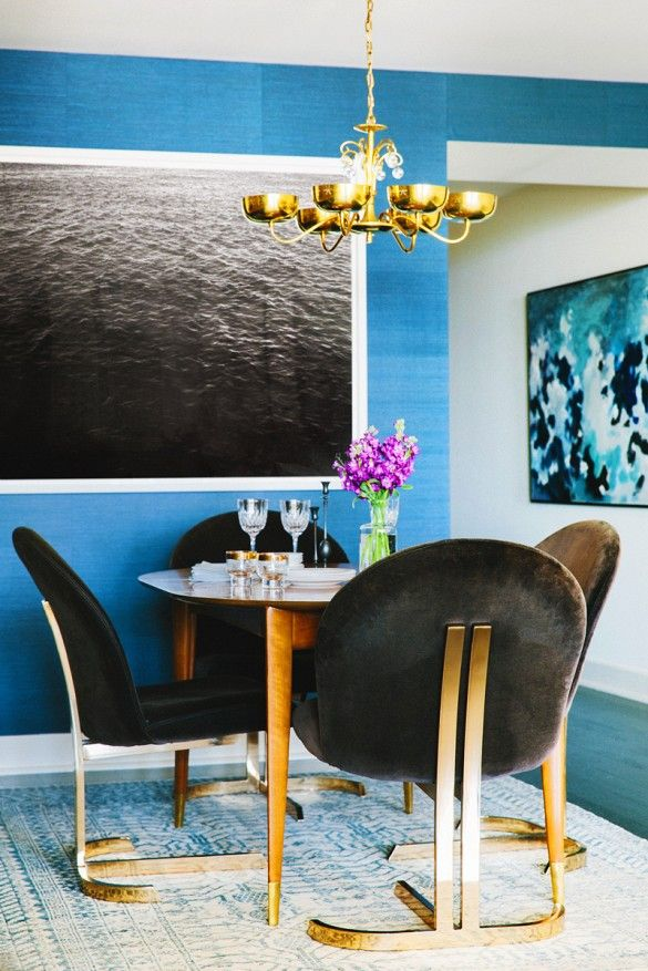 Small dining space with black and brass chairs and large-scale water photography print.