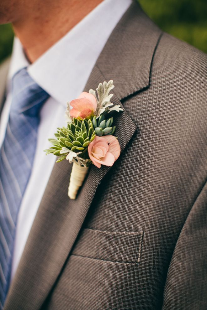 For a farm chic wedding in the autumn, this cleanly arranged boutonniere sheens green with succulents, accented with coral flowers.