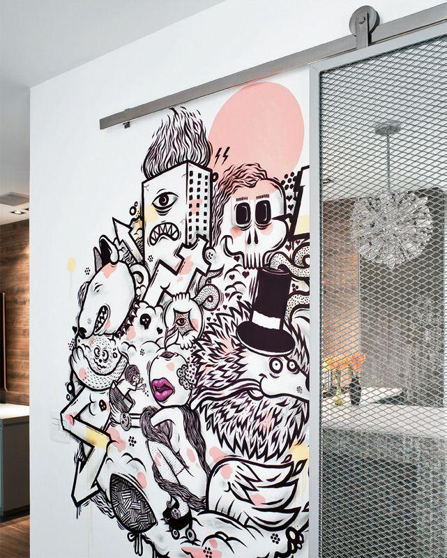 A porta ao lado emprega chapa metálica perfurada (Permetal) associada a um espelho. Esta leva da cozinha à área de serviço e corre num trilho aparente. Ao lado dela, reunindo referências da vida do casal, o artista Pifo elaborou um grafte na parede próxima à bancada.
