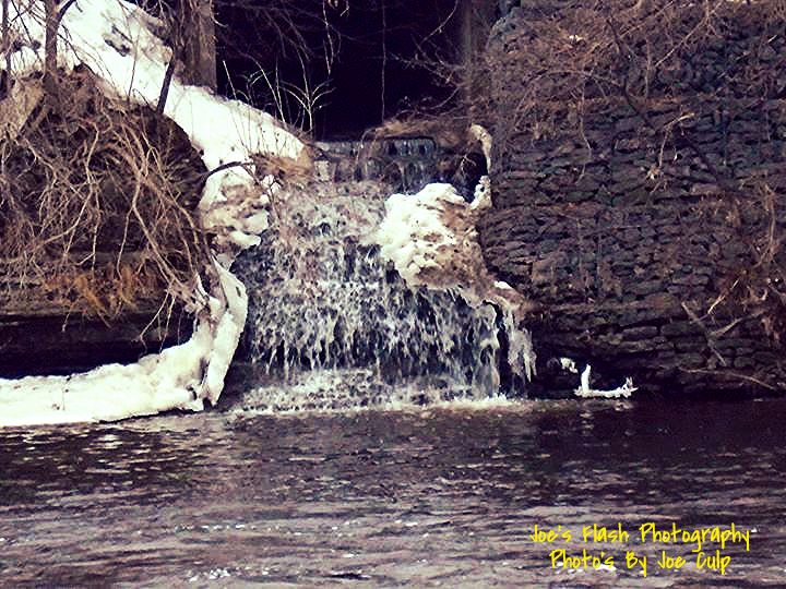 Waterfalling into the Moira river from this manhole Belleville Ontario