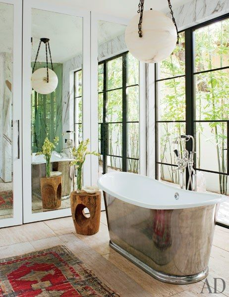 A unique light fixture hangs above the burnished nickel tub   archdigest.com