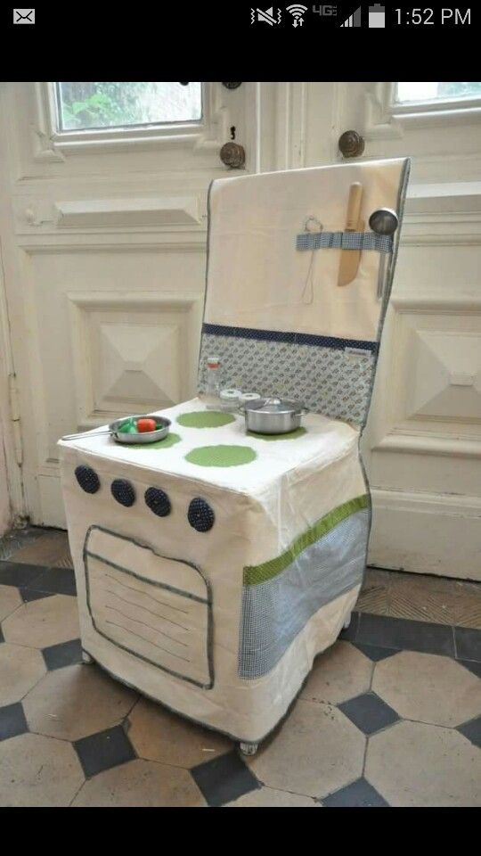 Fabric play kitchen over a chair. Very cute! Easy to store when not in use. Better than those big bulky plastic play kitchens.