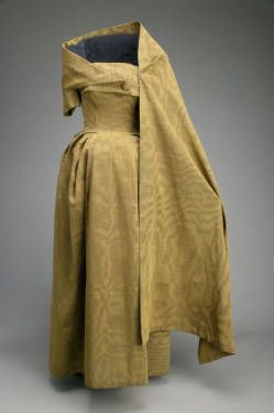 Evening dress and stole, 1953. Ribbed silk moiré. Christian Dior. This unusual evening dress is the Museum's most extreme example of Dior's full-hipped silhouette. The boned understructure supports a system of pleats over the exaggerated hips. The matching one-sleeved wrap has a large hook and eye on the left, attaching it to the strapless dress. The wrap is further supported by a small belt attached with one button.