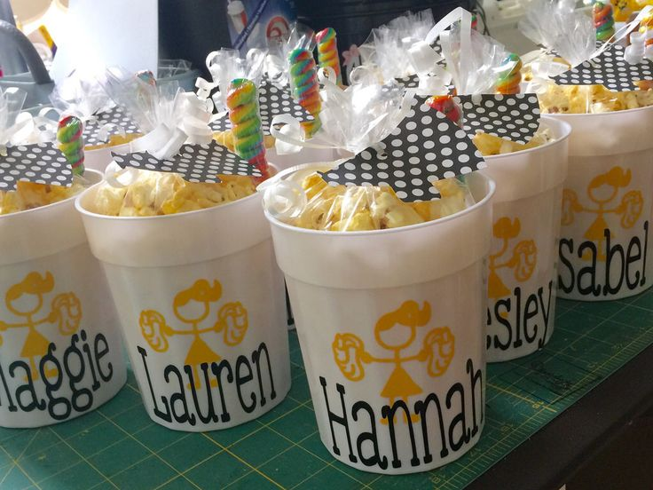 Personalized cups with popcorn and rainbow sucker treats for cheer camp swag bags