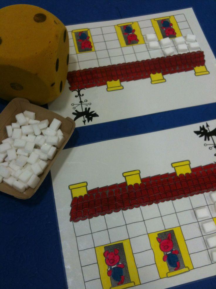Thème des 3 petits cochons. But du jeu : mettre les briques (morceaux de sucre) sur la maison des 3 petits cochons, en fonction du lancé de dé. Possibilité de mettre 1 loup sur une face du dé. Si on tombe sur le loup, on doit enlever toutes les briques déjà posées et recommencer.