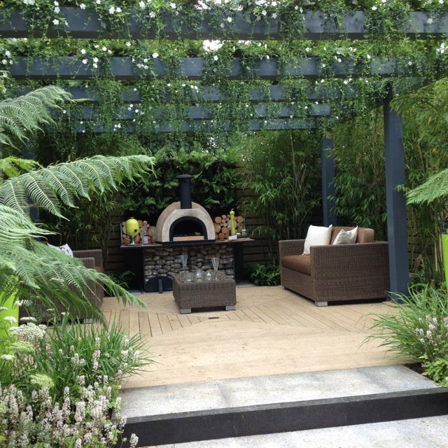 I love the ambience of the decking and draping vines. Must have an outdoor pizza oven