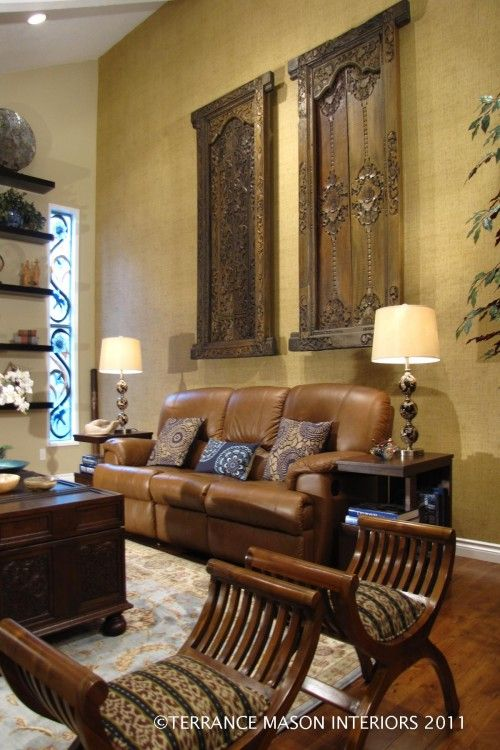 A Pair Of Exotic Doors Hung Behind The Sofa Compliments The Wood Furniture  And Brown Sofas