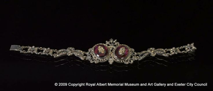bracelet - This silver bracelet is decorated with studs of cut steel and has two cabochon amethysts with insets. The studs form a floral design. This type of design was popular in France during the reign of Louis XV (1710 - 1774) and may well have been brought over to England from the continent. Many of the studs are now missing but it is still a beautiful piece of jewellery. - Royal Albert Memorial Museum & Art Gallery, Exeter