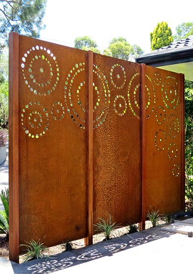 Laser cut screening - Dots (custom). This triple panel feature provides a rustic privacy wall whilst also enclosing and creating a front courtyard for this clients property. Weathering steel panels are supported by hardwood timber posts and will form a lovely backdrop to the recently planted garden as it matures.