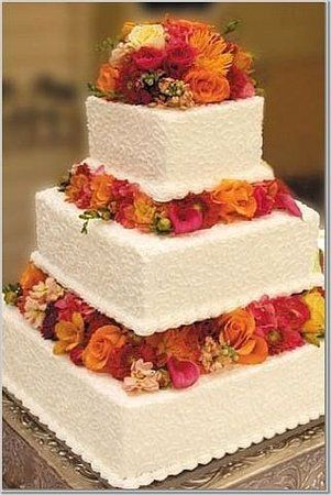 Intricate scrolls and lots of fresh flowers. This 3-tier, white wedding cake features a plethora of fresh flowers in hot colors of fuschia, hot pink, magenta, orange, tangerine, and yellow.