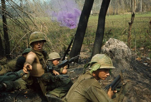 An American soldier turns to give instructions as firing continues in front of him. La Drang, 1965.