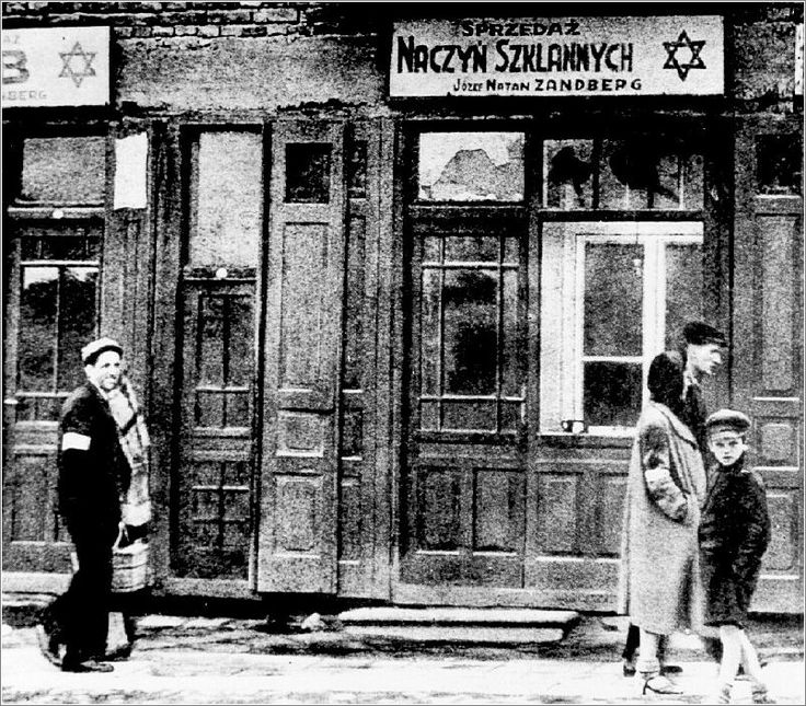 Jews on a street in the Radom ghetto, beside a glazier's shop.