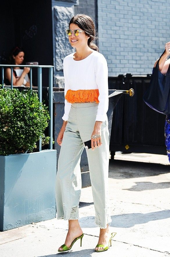 Leandra Medine in a cropped white tee with orange tassel trimming, ripped boyfriend jeans and green satin heels
