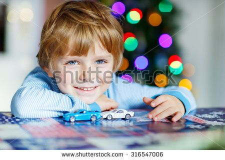 Adorable kid boy playing with cars and toys at home, indoor. funny child having fun with gifts. Colorful christmas lights on background. Family, holiday, kids lifestyle concept. - stock photo