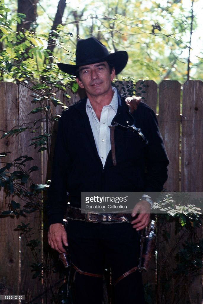 Actor James Drury poses for a portrait holding a gun and wearing a cowboy hat for a portrait session in circa 1980 in Los Angeles, California.