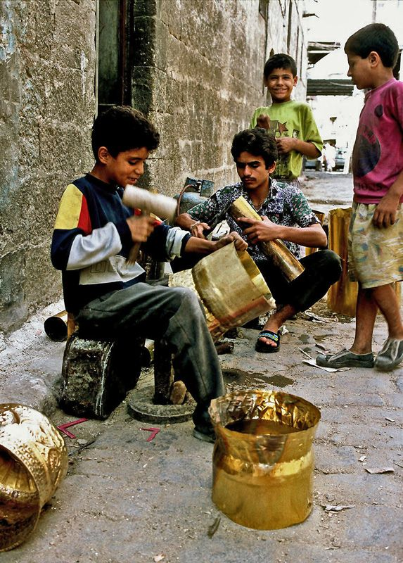 When Syrian eyes were smiling - Aleppo, Halab - .Syria -Photographer's Note . This is from a narrow alley in the old part of Aleppo in northern Syria, taken in September 1995. Two boys are learning a trade, the others seem to be just hanging around, keeping company.
