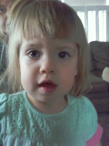 In Rhode Island, a woman took a cell phone pic of her 22 month-old niece, Penny, while babysitting her alone. After looking at her photo and seeing the woman behind Penny (who wasn't there at the time), she had it examined but no tampering was detected. She has since compared family photos and realized that it looks a lot like her deceased great grandmother.