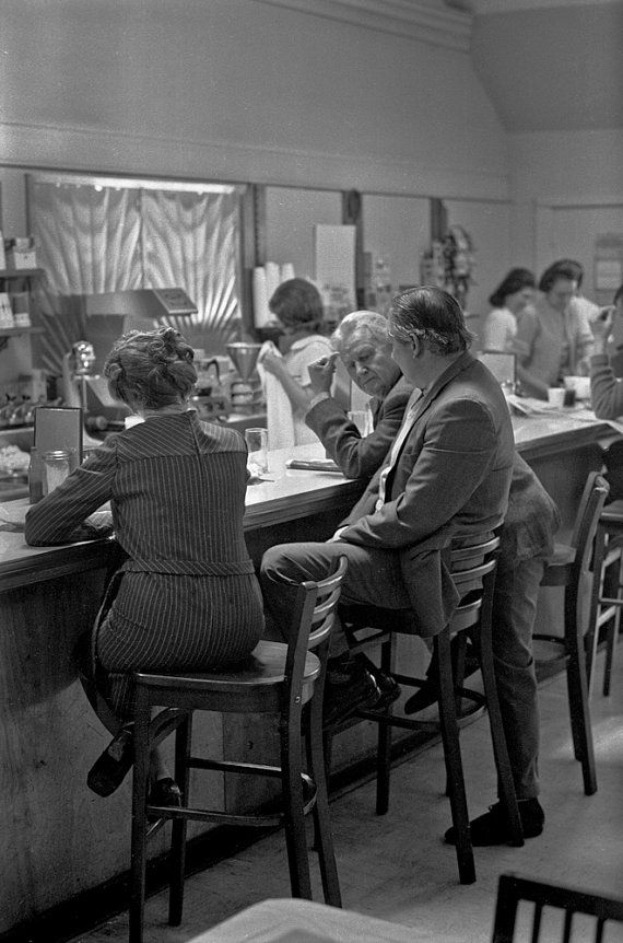 Friends talking at the lunch counter of the Nook Restaurant in Charlottesville Virginia in the 70s- a black and white photograph