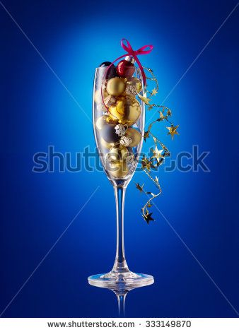 Champagne glass filled with colorful holiday ornaments. Christmas decoration on blue background