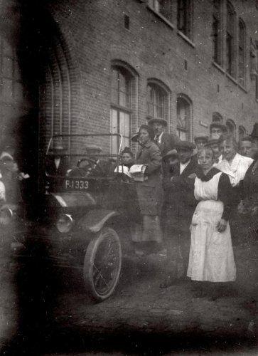 Vrouwenkiesrecht. Vrouwen gaan in Maastricht voor het eerst stemmen. Een auto waarin vrouwen met stembiljetten/of propagandamateriaal staat bij de ingang van een gebouw. Rechts (dienst?)meisjes in een schort en daarachter staan enkele jongemannen. Maastricht, Nederland, 1920.
