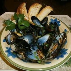 This is a simple recipe.  Most of the work is preparing the mussels; cooking takes very little time.  When you have finished eating the mussels, dip bread in the buttery wine sauce.