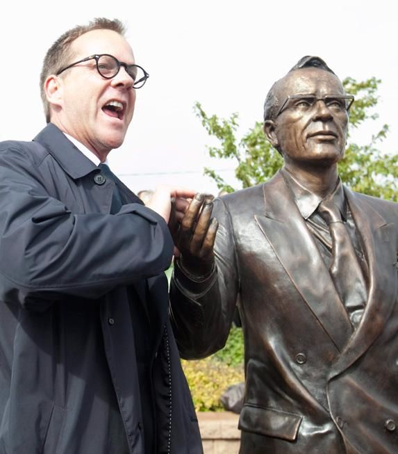 Actor Kiefer Sutherland poses with a life-sized statue of his grandfather Tommy Douglas, in Weyburn, Sask. Douglas was the premier of Saskatchewan and the founder of medicare in Canada.