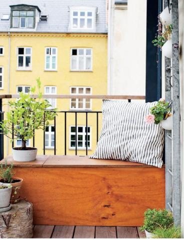 A deep lidded bench does double-duty as a place to sit and storage for throw pillows and gardening gear on an apartment balcony.