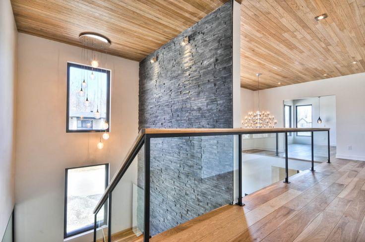 Grande escalier avec mur décoratif en pierre. Escalier avec rampe verre et en bois
