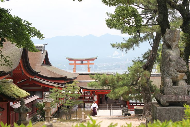 Shelby Barbe: This photo was taken on the Island of Miyajima(宮島)located in Japan's well known Hiroshima(広島). The photo was taken from up the back of the shrine further up the mountain side. It shows a good display of natural Japan along with the Shrine tori gates and even a priest doing his duties around the inner shrine.